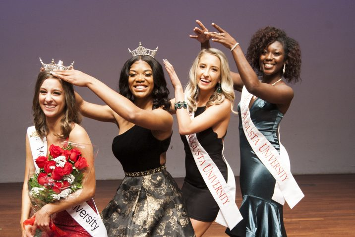 "All four Miss Augusta University winners pose for a photo, ""crowning"" one another"