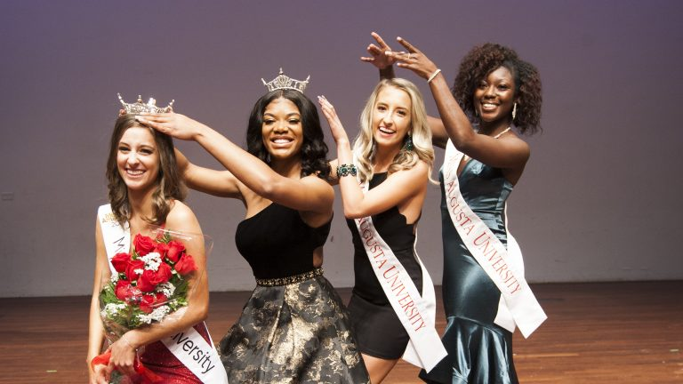 """All four Miss Augusta University winners pose for a photo, """"crowning"""" one another"""