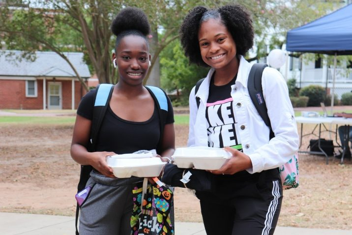 Two students smiling at camera, holding to-go boxes and goodie bags