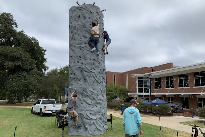 Students climb rock wall