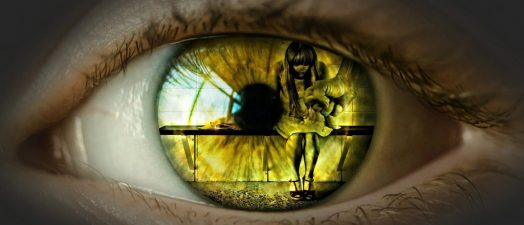 up close view of an eye looking and seeing a girl sitting down