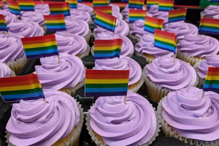 Photo of vanilla cupcakes with purple frosting. Cupcakes are decorated with mini LGBTQ+ pride flag on toothpicks.