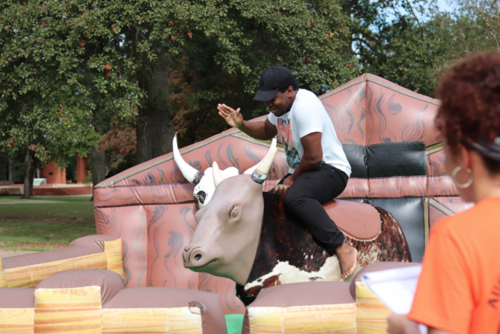 student riding a mechanical bull