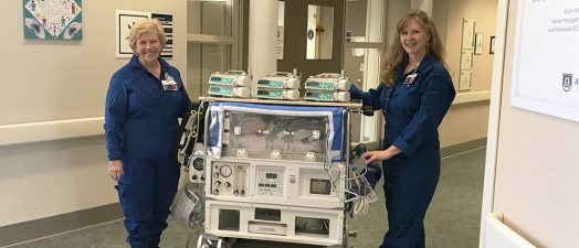 Two transport nurses dressed in blue coveralls roll a baby isolette on wheels
