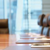 Closeup of a boardroom table and six chairs