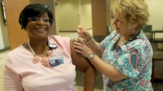 Nurse giving woman a flu shot.