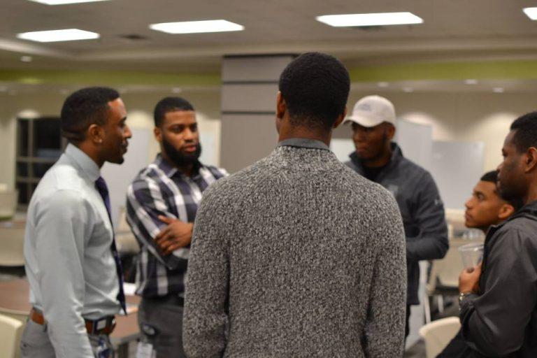 men standing in a circle talking