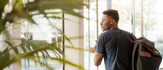 student walking through a door