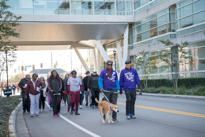A photo of people walking under the Georgia Cancer Center's Collaborative Connector.
