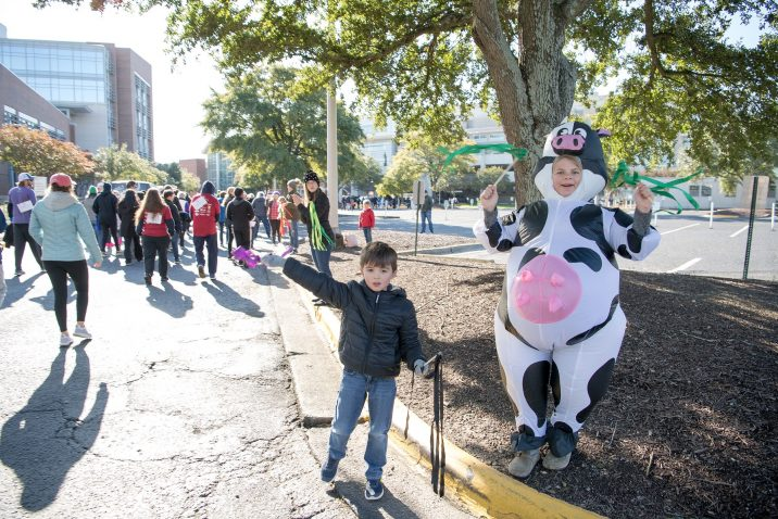 A photo of a person dressed in a cow costume cheering people on.