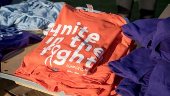 A picture of a t-shirt showing the Unite in the Fight Against Cancer logo