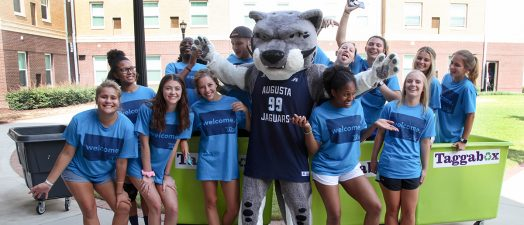 students smiling with the school mascot