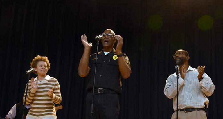 three people singing on stage
