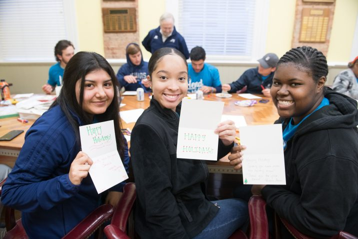 students smiling with handmade holiday cards