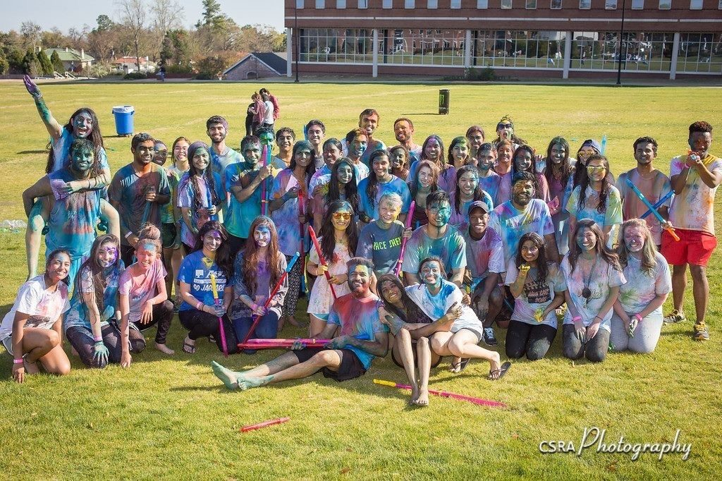 Large group of students covered in color powder, posing for photo on lawn