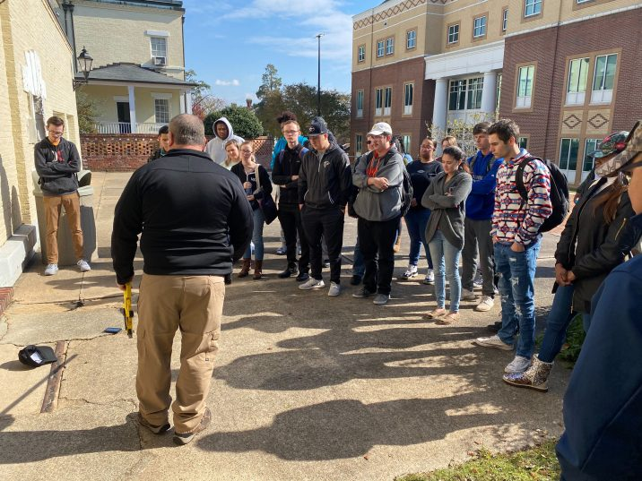 man teaching students outside