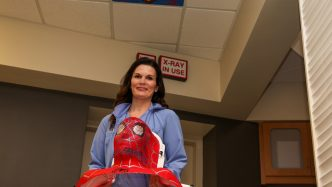 Woman holding a Spider-man mask used for radiation treatment