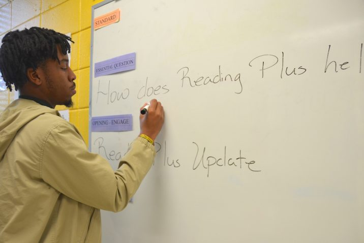 Teacher writing on a board.