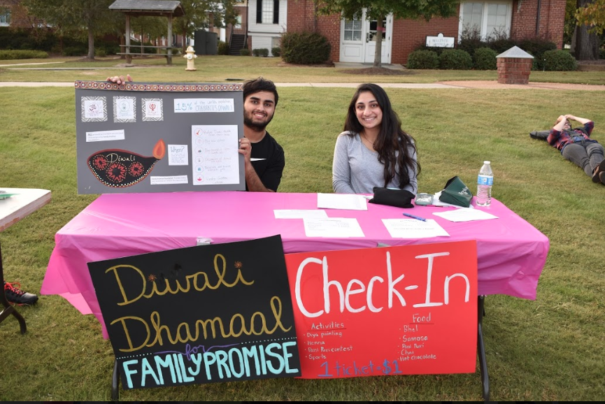 2 students sit at check-in table at Diwali event