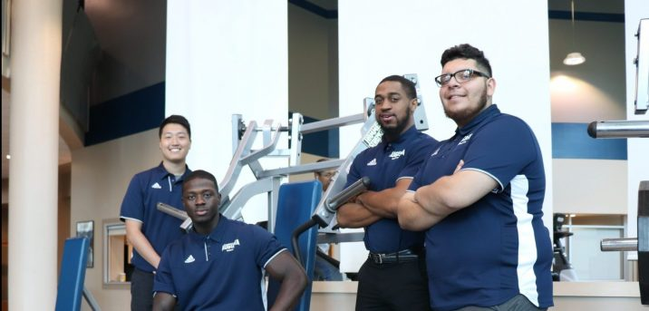 Four male students in matching blue polos, posing in front of fitness equipment
