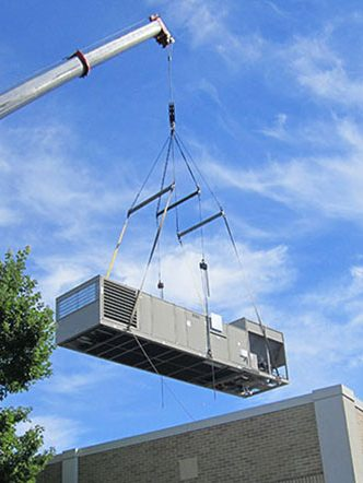 crane lifts chiller over building