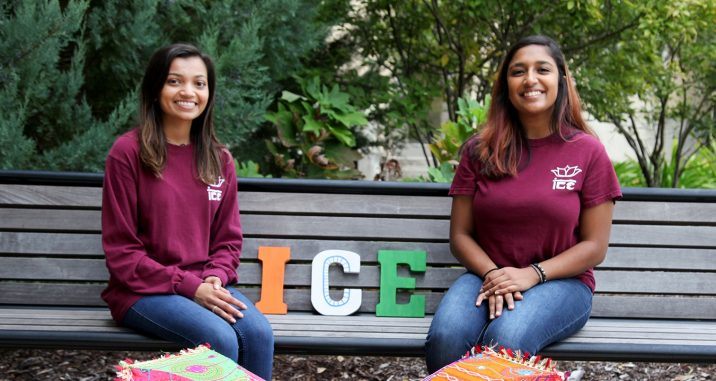 Two female students sitting on a bench in matching club T-shirts.