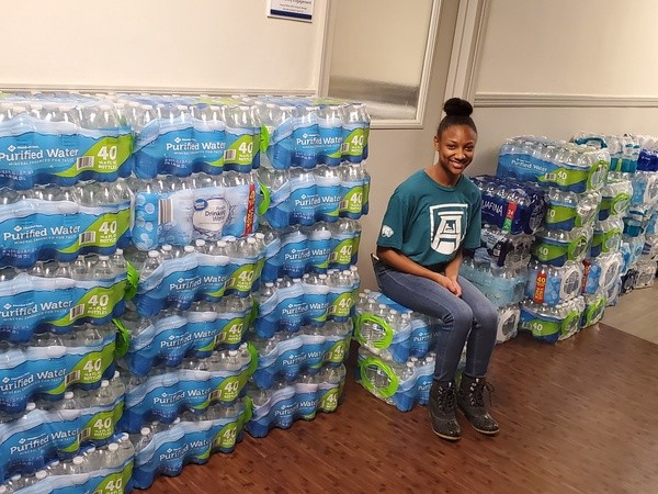 student posing with cases of bottled water