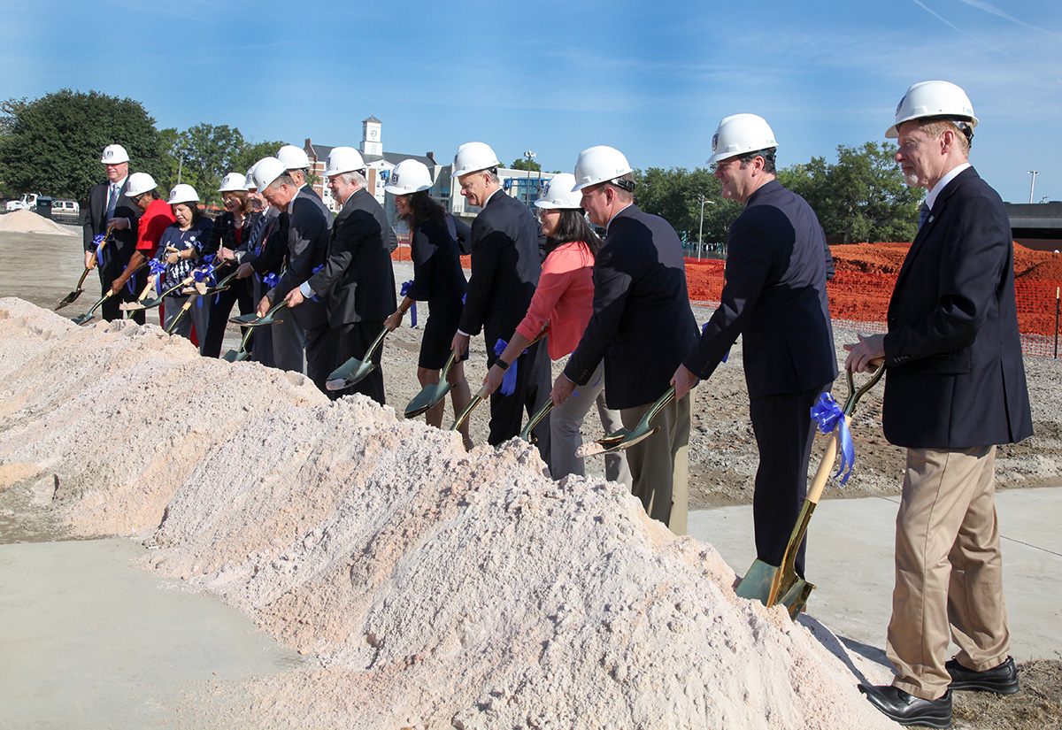 people with shovels standing in front of a dirt pile