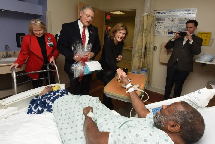 man greeting patient in hospital bed