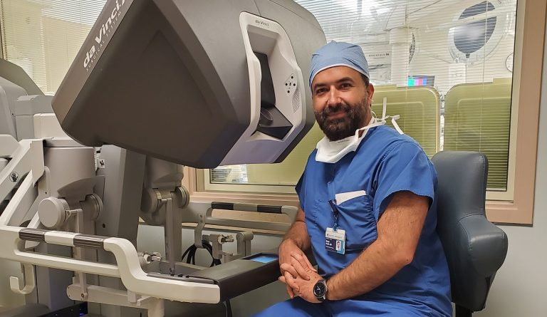 A doctor sitting at a console where doctors perform robotic surgeries.