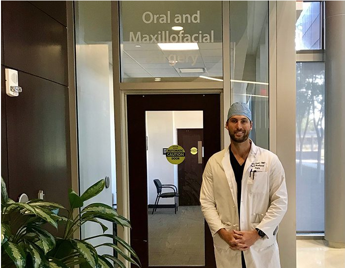 man standing in front of a dental office