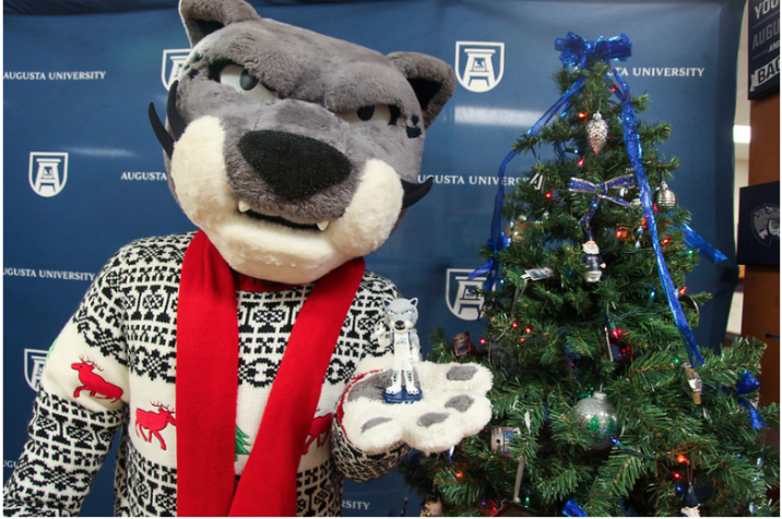 Augustus the mascot standing next to a Christmas tree
