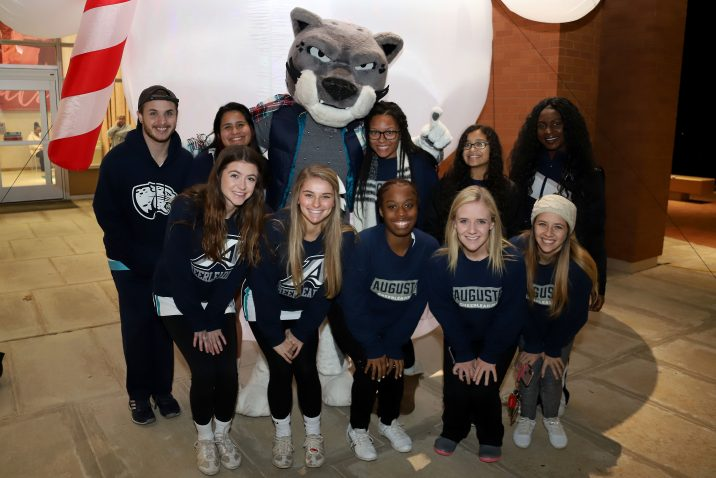 group of cheerleaders smiling with Augustus the mascot
