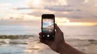 Hand and phone taking photo of ocean