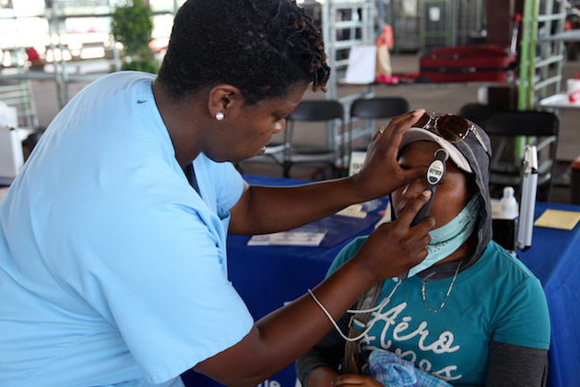 A nurse checking the eyesight of a patient at a health fair.