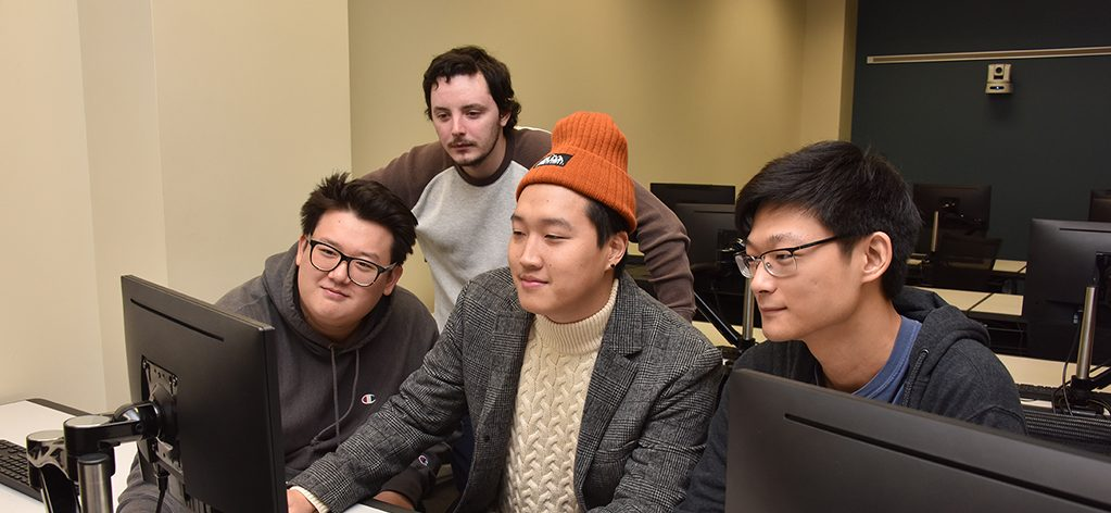 Four men looking at a computer