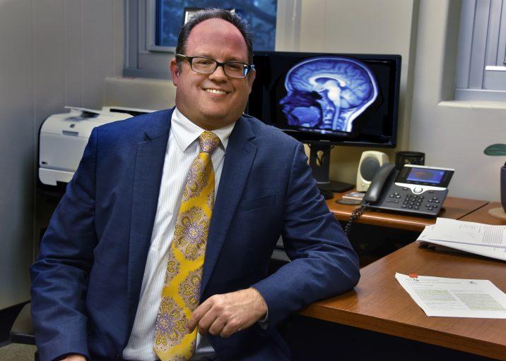 man in suit smiling at desk