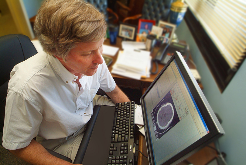A man sitting in front of a computer looking at an image of a brain.