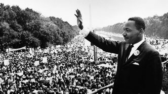 black and white photo of a man waving to a crowd full of people