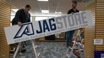 Two men hang a sign identifying the Augusta University JagStore.