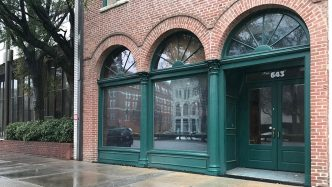 brick building with green arches, three windows