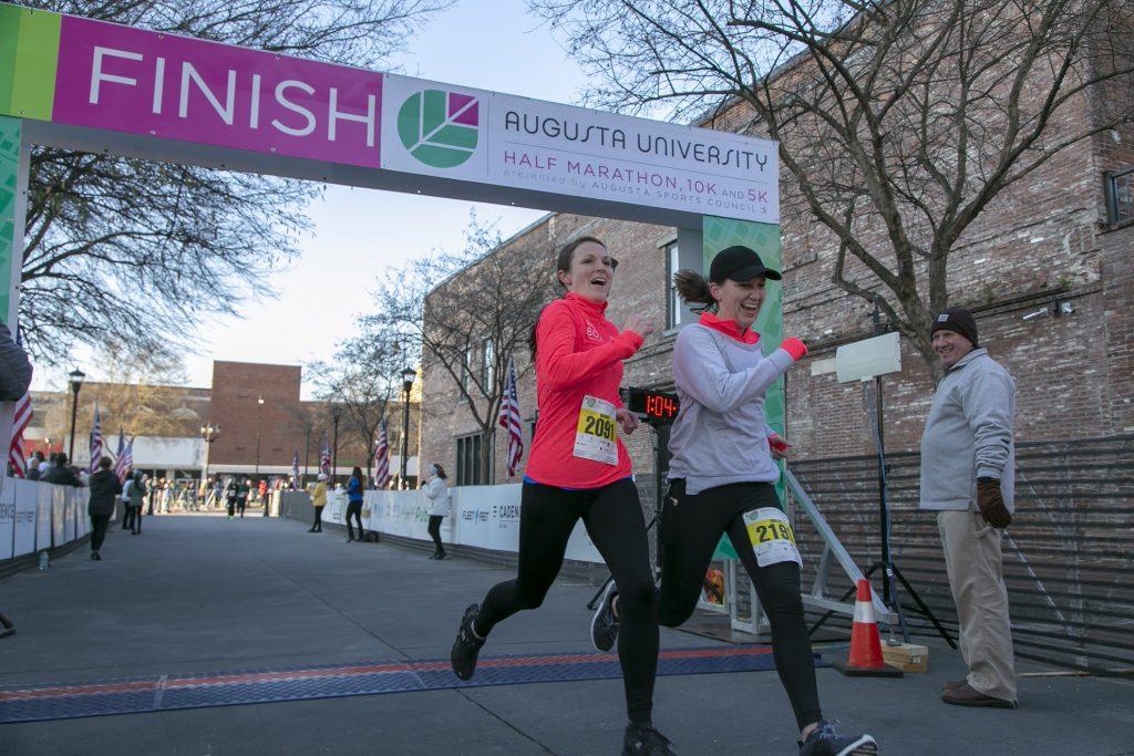 marathon runners go through finish line