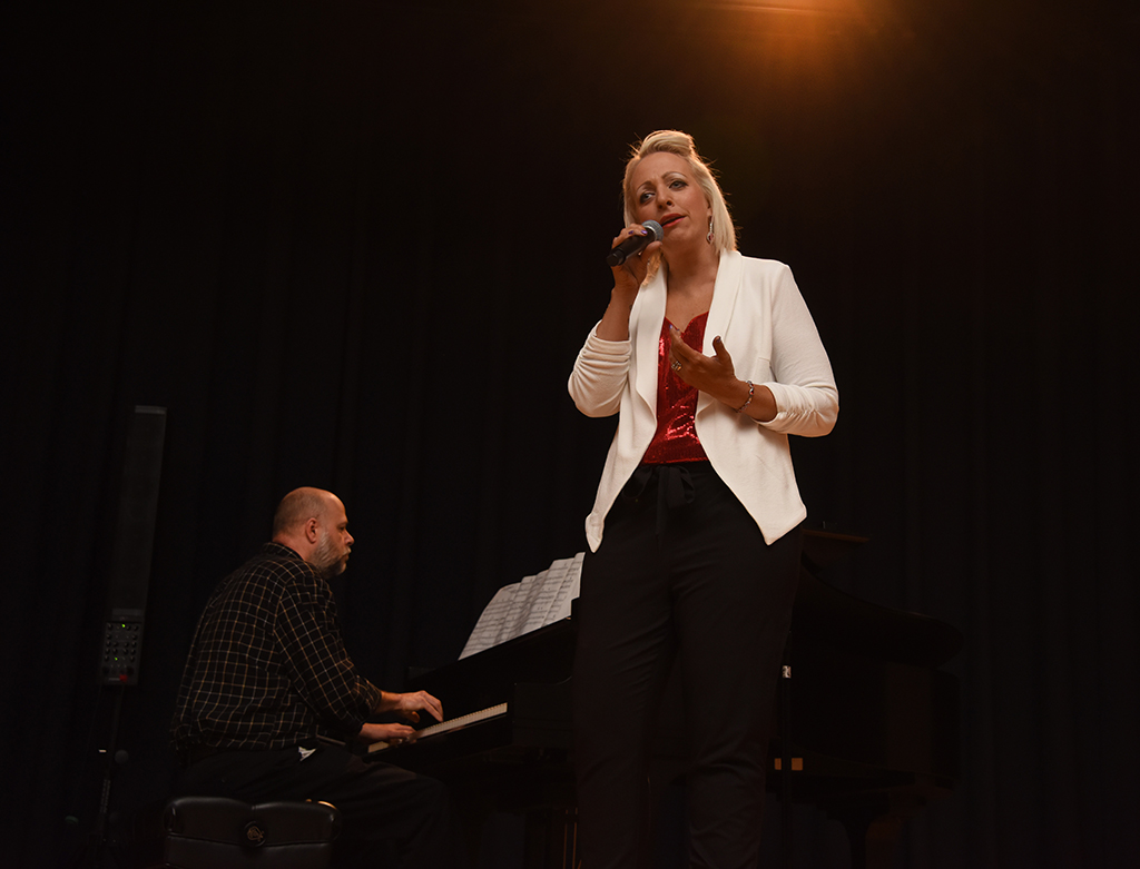 Woman singing and man playing piano