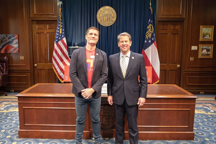 Governor Brian Kemp stands next to the executive director of Paceline Ride