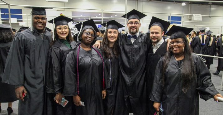 group of 7 graduates in black caps and gowns