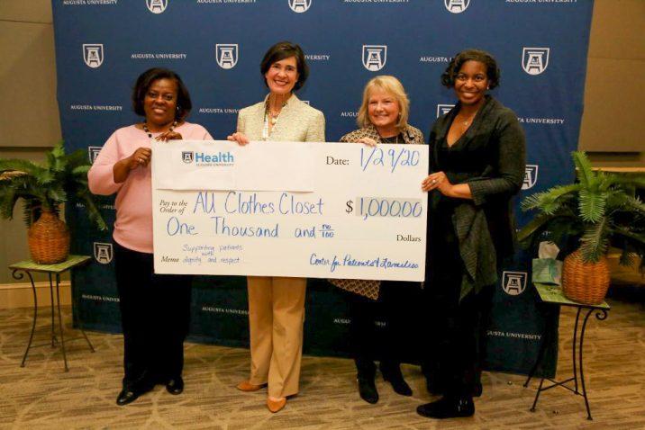 Four women holding giant check