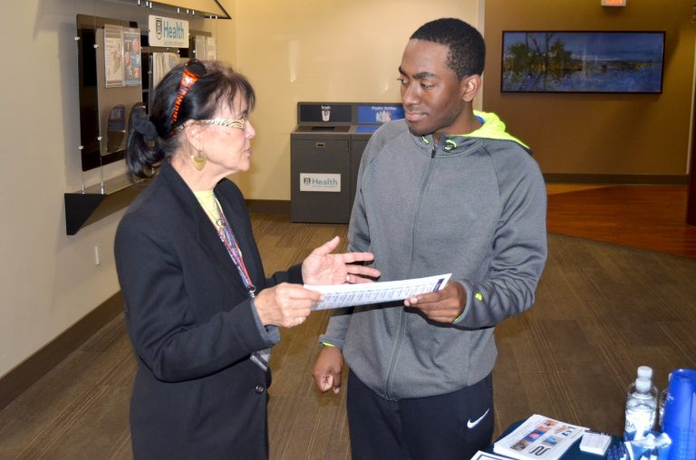 Woman holding a piece of paper talking with a young adult