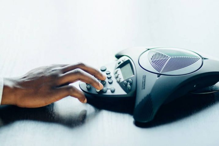 hand on conference phone speaker