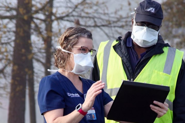 person with mask looking at clipboard