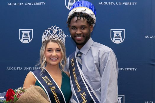man and woman smiling for photo, wearing crowns and sashes